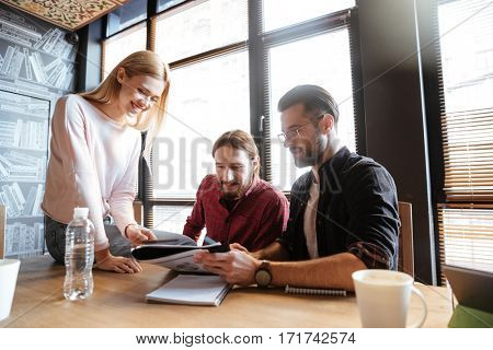 Photo of smiling colleagues sitting in office and coworking. Working with documents.