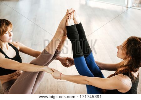 Two peaceful attractive young women meditating and doing acro yoga in studio