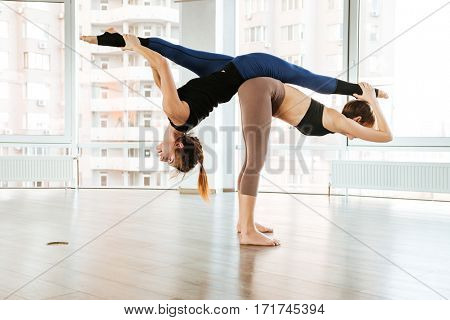Two slim young women doing acro yoga together in studio