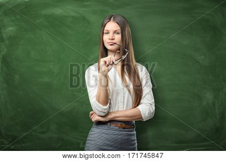 Young pretty woman is holding her glasses and smiling on green chalkboard background. Advertising concept. Having an idea. Development and knowledge