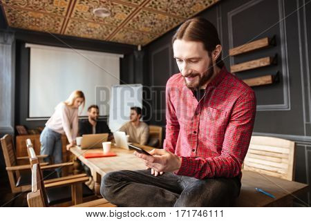 Image of smiling man sitting in office. Coworking. Looking at phone.