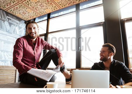 Image of young smiling colleagues sitting in office and coworking. Working with documents.