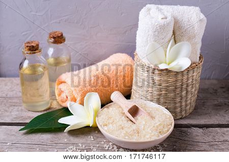 Sea salt in bowl towels bottles with aroma oil and flowers on vintage wooden background. Selective focus.