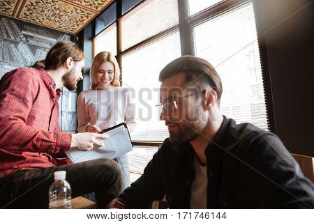 Image of young happy colleagues sitting in office and coworking. Working with documents.