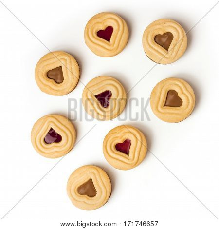 An overhead shot of cocoa and jam cookies with heart-shaped fillings on white background