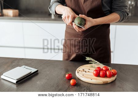 Cropped picture of young woman standing in kitchen cut the tomatoes and avocado.