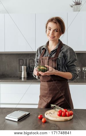 Photo of young cheerful woman standing in kitchen cut the tomatoes and avocado.