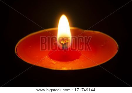 red candle and candlelight with isolated black background