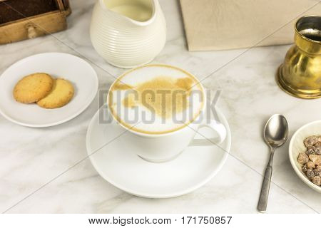 A cup of coffee with milk with butter cookies and a milk jar on a white marble table, with a place for text. Selective focus