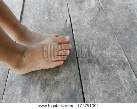 Child dirty feet standing on a bed of brown wood.
