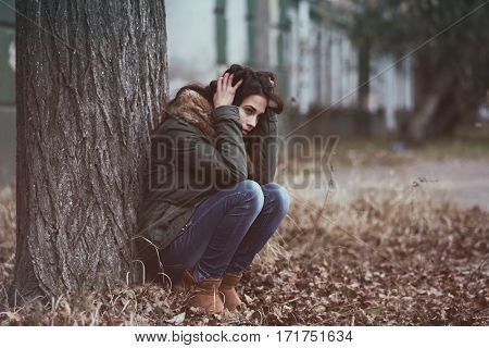 Depressed young woman sitting under tree