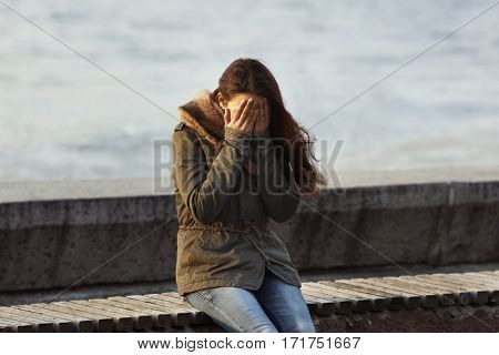 Depressed young woman sitting on bench