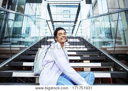 young cute indian girl at university building sitting on stairs reading a book, wearing hipster glasses, lifestyle people concept close up