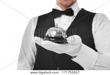Young waiter with service bell on white background