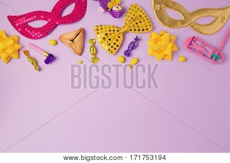 Purim holiday concept with carnival mask and party supplies on purple background. Top view from above with copy space
