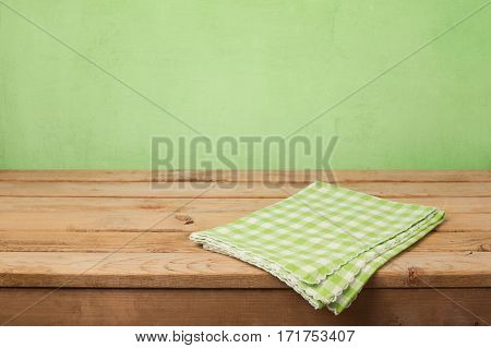 Empty wooden deck table with checked tablecloth over green wall background for product montage display