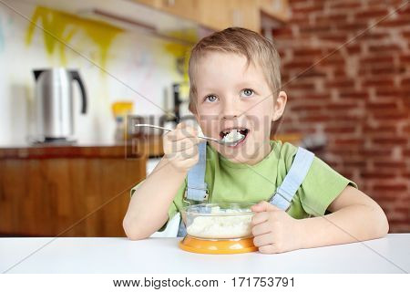 Little boy having breakfast in the kitchen. Five years boy eats rice porridge