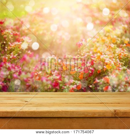 Empty wooden deck table over flowers bokeh background for product monatge display. Spring or summer season concept