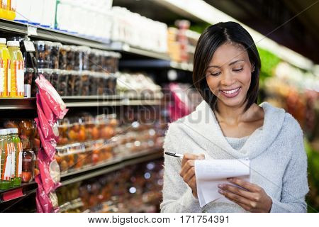 Smiling woman writing in notepad at grocery section of supermarket