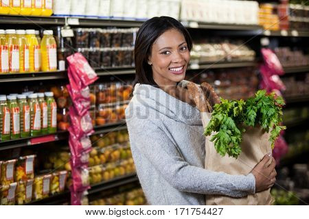Portrait of smiling woman holding a grocery bag in supermarket