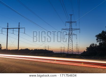 High voltage electricity pylon system and tracks from traffic