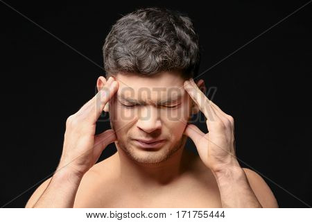Handsome young man suffering from headache on dark background