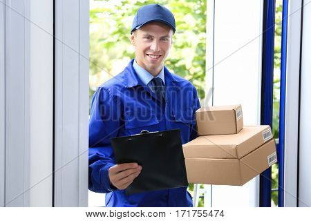 Courier holding packages and clipboard in doorway