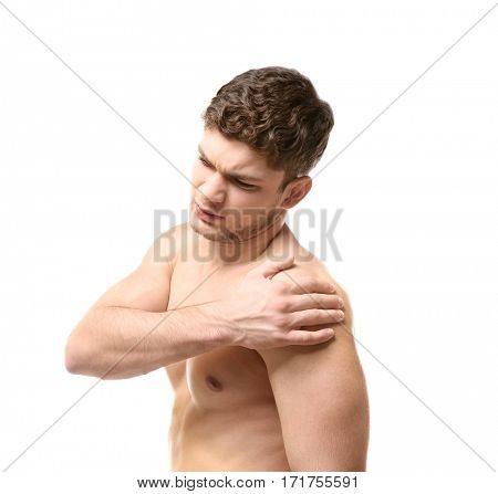 Young man suffering from pain in shoulder on white background