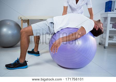Physiotherapist assisting man with exercise ball in clinic