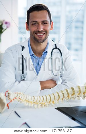 Portrait of smiling physiotherapist sitting with spine model in clinic