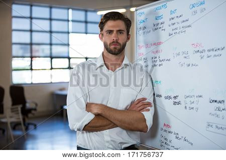 Portrait of confident businessman leaning on whiteboard in meeting room