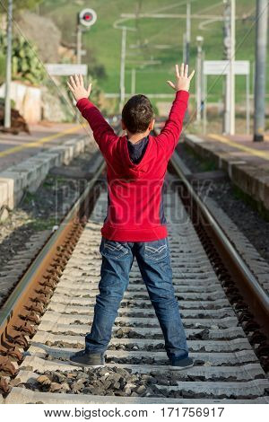 Young hitchhiker waiting of the train standing on railway