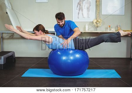 Physiotherapist assisting woman on exercise ball in the clinic