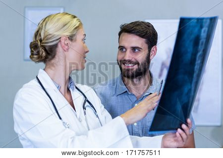 Physiotherapist showing x-ray to a patient in clinic