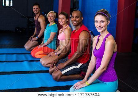 Portrait of smiling people exercising while kneeling in gym