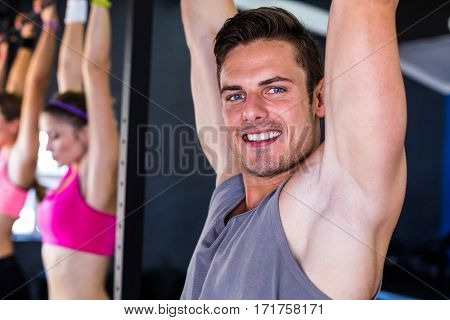 Portrait of smiling man doing chin-ups while hanging in gym