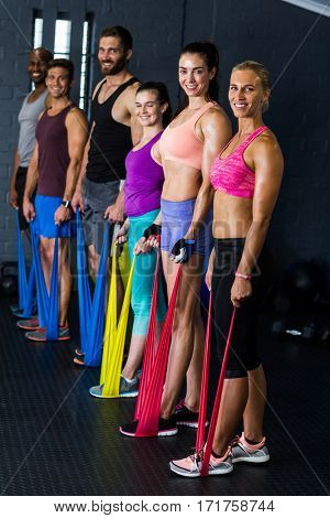 Portrait of male and female athletes exercising with resistance band in gym