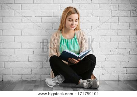 Beautiful young woman with book sitting on floor near brick wall