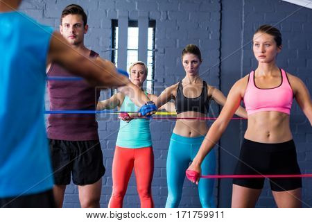 Male and female athletes looking at trainer while exercising with resistance band