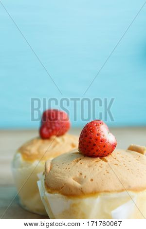 close up bakery cup cake with strawbery on wooden background