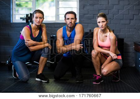 Portrait of young determined athletes kneeling in gym