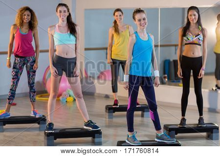 Group of women standing on aerobic stepper in gym