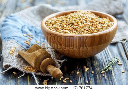 Whole Grain Oats In A Wooden Bowl And Scoop.