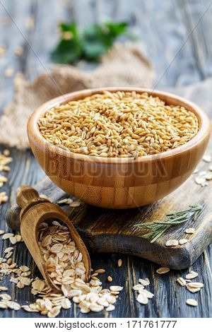 Wooden Bowl With Whole Grain Oats And Oatmeal Scoop.