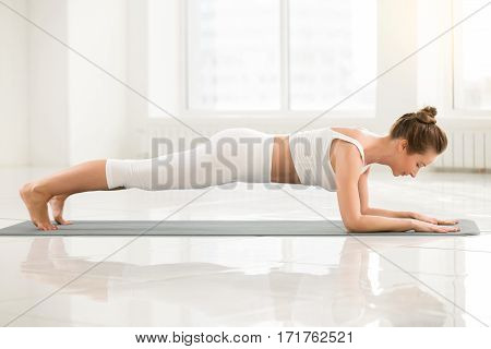 Young attractive yogi woman practicing yoga, standing in Dolphin Plank exercise, phalankasana pose, working out, wearing sportswear, sport bra, pants, indoor full length, white color room background