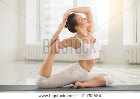 Young attractive yogi woman practicing yoga, sitting in Eka Pada Rajakapotasana exercise, Mermaid pose, working out, wearing sportswear, sport bra, pants, indoor full length, white color background