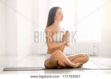 Young attractive yogi woman practicing yoga, sitting in Sukhasana exercise, Easy Seat pose with namaste, working out, wearing sportswear, sport bra, shorts, indoor full length, white color background