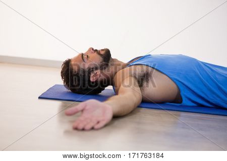 Man in yoga corpse pose in fitness studio