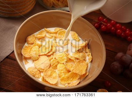 Pouring milk into tasty cornflakes on wooden background