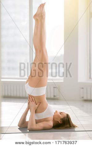 Young attractive yogi woman practicing yoga, standing in Salamba Sarvangasana exercise, supported Shoulder stand pose, working out, wearing sportswear, sport bra, shorts, full length, white background